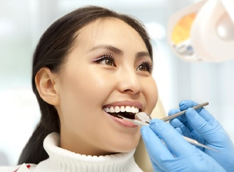 Woman in dental chair at cleaning and checkup appointment.