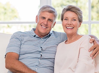 Couple smiling after getting dental implants in Prince Albert