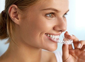 woman putting on invisalign