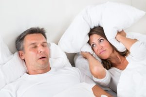 woman covering ears pillow husband snoring